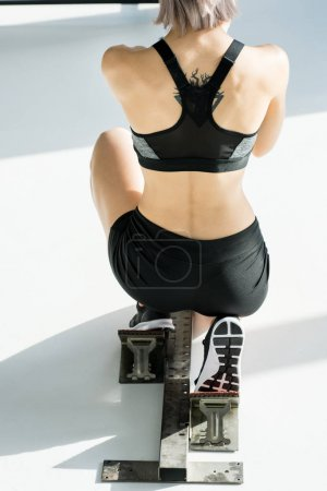 Photo for Back view of sporty woman in starting position on grey - Royalty Free Image