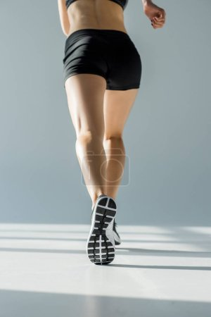 Photo for Back view of running woman in sportive clothing on grey - Royalty Free Image