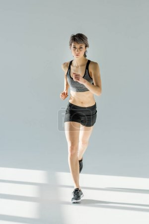 Photo for Front view of running woman in sportive clothing on grey - Royalty Free Image