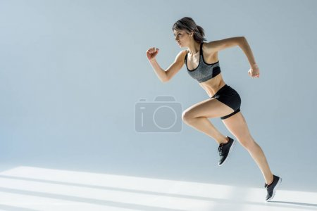 Photo for Side view of running woman in sportive clothing on grey - Royalty Free Image