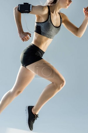 Photo for Side view of running sporty woman isolated on grey - Royalty Free Image