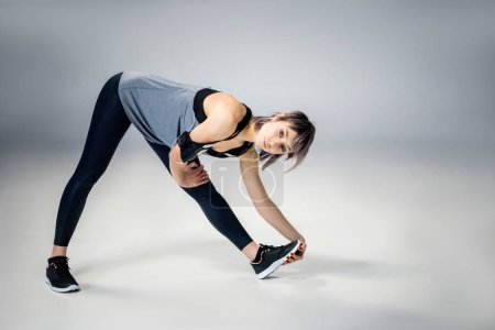 Photo for Woman in sportive clothes stretching  isolated on grey - Royalty Free Image