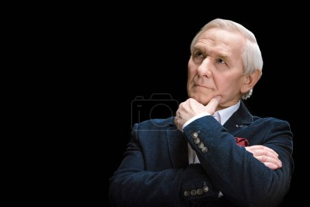Photo pour Thoughtful senior man with hand on chin looking away  isolated on black - image libre de droit