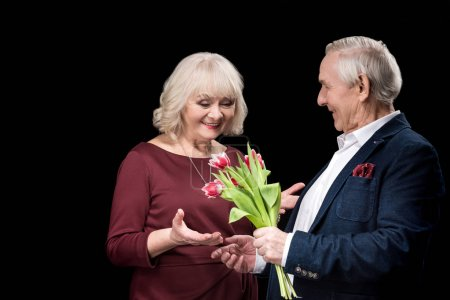 Photo pour Smiling senior man presenting tulips bouquet to happy woman, international womens day concept isolated on black - image libre de droit