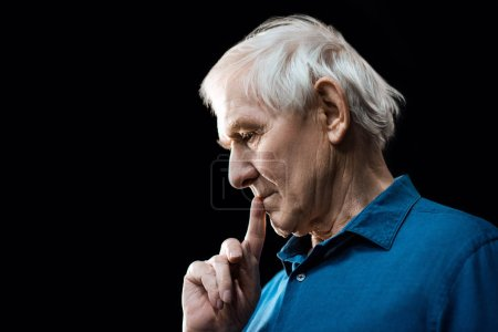Photo pour Portrait of pensive senior man  isolated on black - image libre de droit