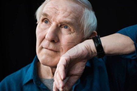 Photo pour Portrait d'homme âgé écoutant regarder au poignet isolé sur noir - image libre de droit