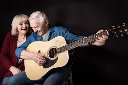Photo for Side view of senior man playing guitar with wife near by  isolated on black - Royalty Free Image
