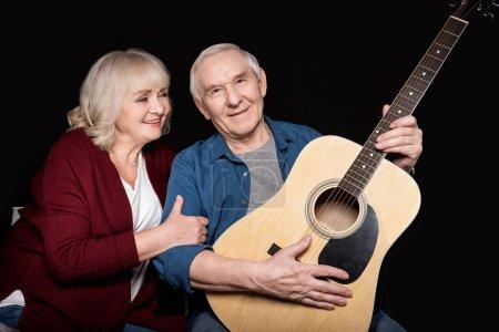 Photo pour Portrait d'un homme âgé tenant une guitare avec sa femme à proximité isolé sur noir - image libre de droit