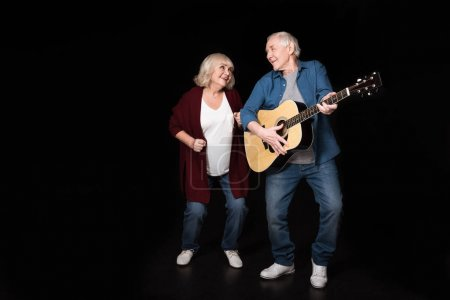 Photo for Senior man playing guitar while woman dancing near by isolated on black - Royalty Free Image