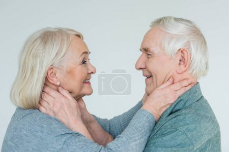 Photo for Side view of smiling senior couple looking at each other on white - Royalty Free Image