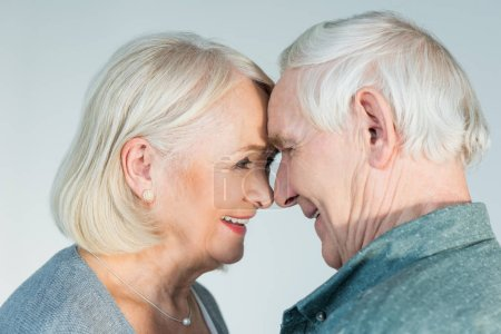Photo for Side view of smiling senior man and woman looking at each other on grey - Royalty Free Image