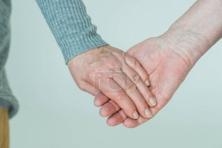 Photo for Partial view of senior couple holding hands on grey - Royalty Free Image
