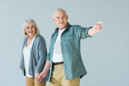 Photo for Portrait of smiling senior couple holding hands while man pointing away - Royalty Free Image