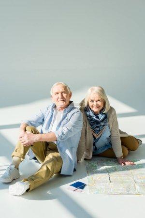 Photo pour Couple de personnes âgées assis sur le plancher avec voyage carte et passeports, voyager concept - image libre de droit
