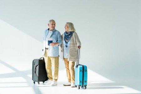 Photo pour Heureux couple senior avec voyageant des sacs, des passeports et des billets, le concept de voyage - image libre de droit