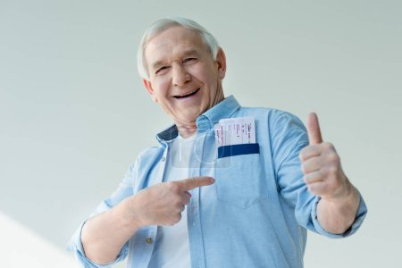 Photo for Portrait of happy senior man pointing to passports and tickets in pocket, traveling concept - Royalty Free Image