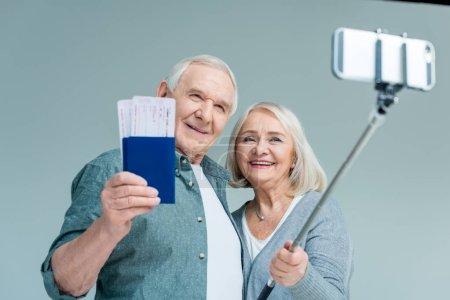 Photo pour Portrait de couple âgé souriant avec passeports et billets faisant selfie sur smartphone, concept de voyage - image libre de droit