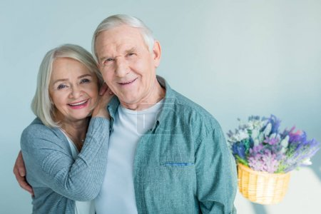 Photo for Portrait of happy senior woman bonding to husband on grey - Royalty Free Image