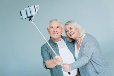 Photo pour Portrait de couple âgé souriant faisant du selfie sur smartphone sur gris - image libre de droit