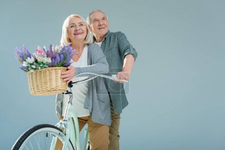 Photo for Portrait of happy senior man and woman with bicycle on grey - Royalty Free Image