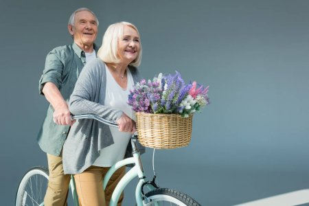 Photo for Side view of smiling senior couple riding bicycle together on grey - Royalty Free Image
