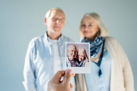 Photo for Portrait of senior man and woman with their photo on foreground - Royalty Free Image
