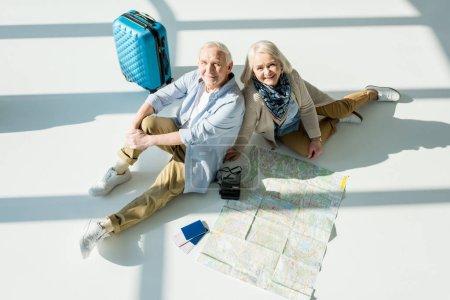 Photo pour Couple de personnes âgées assis sur le plancher avec Voyage sac, carte et passeports, voyager concept - image libre de droit