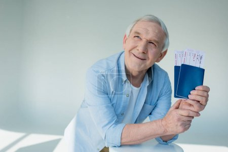 senior man with passports and tickets