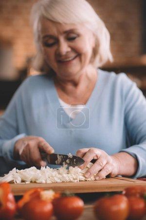Senior woman chopping onions