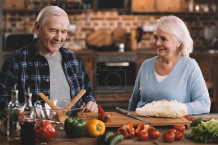 Photo for Portrait of cheerful senior couple resting while making salad at home - Royalty Free Image