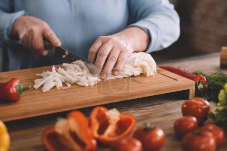 Senior woman chopping onion
