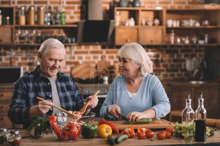 Photo for Portrait of smiling senior couple making salad together in kitchen - Royalty Free Image