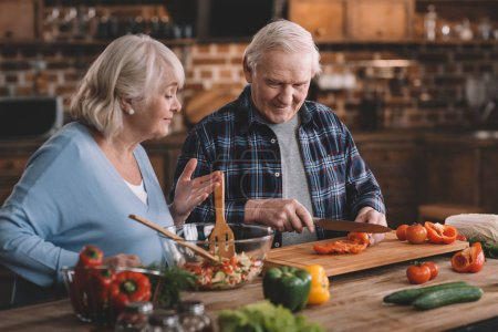 Photo for Portrait of smiling senior man and woman making salad together - Royalty Free Image