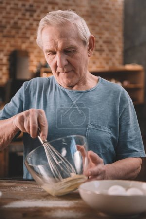 Photo for Smiling senior man whipping cream with whisk in glass bowl - Royalty Free Image