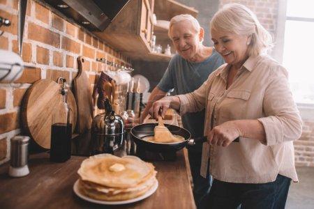 senior couple cooking pancakes