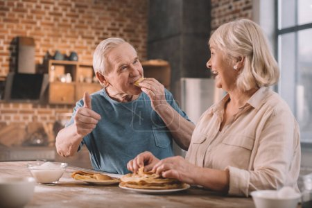 Photo for Senior couple eating pancakes on kitchen at home - Royalty Free Image