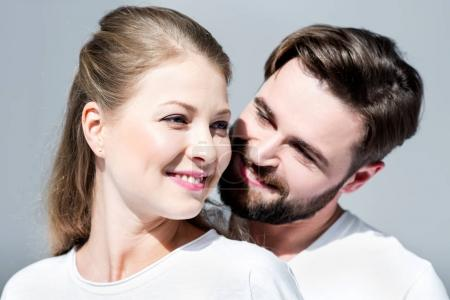 Photo for Happy young couple in white t-shirts standing embracing on grey - Royalty Free Image