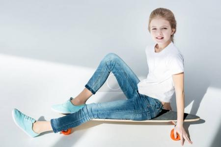 Girl sitting on skateboard