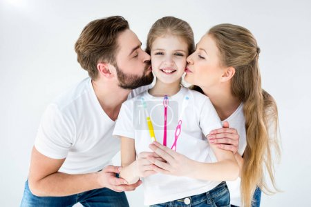 Photo for Happy parents kissing cute little daughter holding toothbrushes - Royalty Free Image