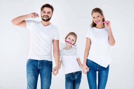 Photo for Happy family in white t-shirts cleaning teeth with toothbrushes on white - Royalty Free Image
