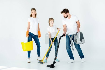 Photo for Parents and little daughter with different cleaning supplies on white - Royalty Free Image