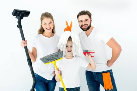 Photo for Portrait of smiling family with various cleaning supplies on white - Royalty Free Image