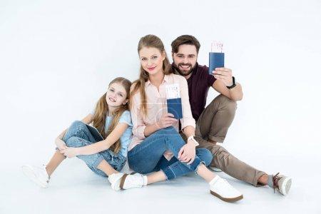 Photo pour Parents souriants avec passeports et billets et fille avec tablette sur blanc - image libre de droit