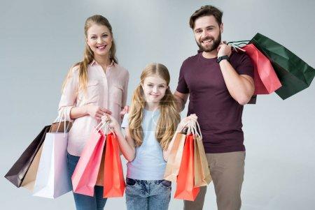 Photo pour Mère, père et fille debout avec des sacs à provisions sur gris - image libre de droit