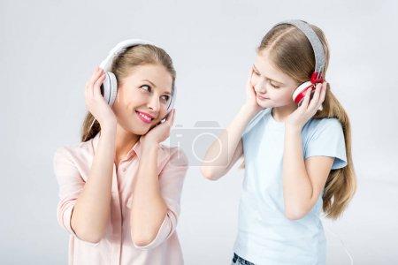 Photo pour Mère et fille écouter de la musique avec écouteurs en studio sur blanc - image libre de droit