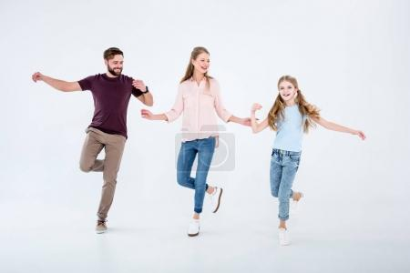 Photo for Mother, father and daughter dancing together in studio on white - Royalty Free Image