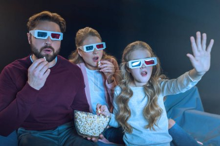 Photo pour Shocked family in 3d glasses watching movie and eating popcorn  isolated on grey - image libre de droit