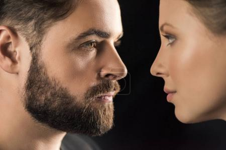 Photo pour Close-up side view of young man and woman looking at each other  isolated on black - image libre de droit