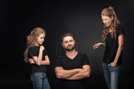 Photo pour Mother and daughter quarreling at father sitting with crossed arms  isolated on black - image libre de droit