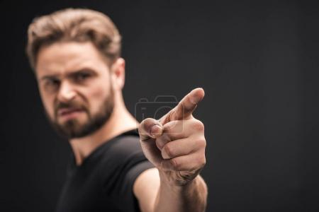 Angry bearded man pointing  isolated on black with...